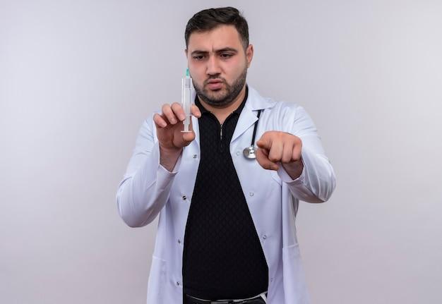 Giovane maschio barbuto medico indossa camice bianco con lo stetoscopio tenendo la siringa che punta con il dito alla telecamera con faccia seria