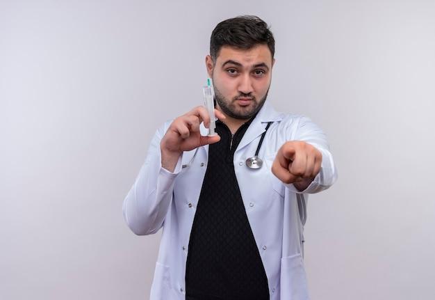 深刻な顔でカメラに指で指している注射器を保持している聴診器で白衣を着ている若いひげを生やした男性医師