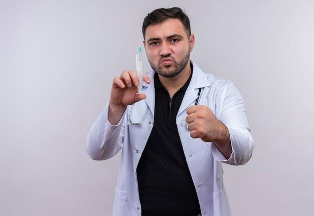 Giovane maschio barbuto medico indossa camice bianco con lo stetoscopio tenendo la siringa sorridente fiducioso pugno di serraggio, concetto vincitore