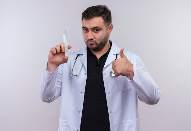 Giovane maschio barbuto medico indossa camice bianco con lo stetoscopio che tiene la siringa sorridente fiducioso che mostra i pollici in su