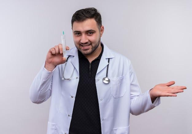 Giovane maschio barbuto medico indossa camice bianco con lo stetoscopio tenendo la siringa sorridente fiducioso