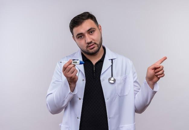 Giovane maschio barbuto medico indossa camice bianco con uno stetoscopio tenendo il termometro che guarda l'obbiettivo con la faccia seria che punta con il dito di lato
