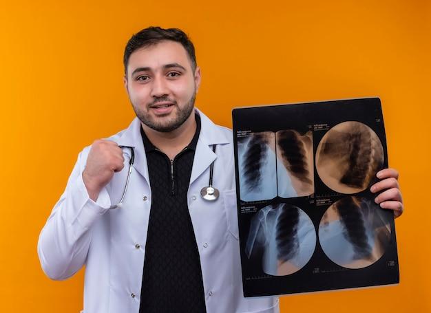 Giovane maschio barbuto medico indossa camice bianco con uno stetoscopio tenendo i raggi x dei polmoni pugno di serraggio felice ed uscito