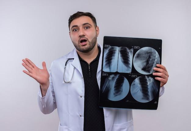 Giovane medico maschio barbuto che indossa camice bianco con lo stetoscopio che tiene i raggi x dei polmoni che sembrano sorpresi e scioccati