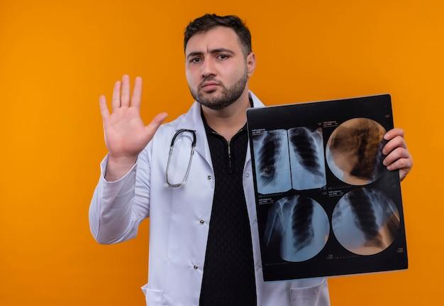 Giovane maschio barbuto medico indossa camice bianco con lo stetoscopio che tiene i raggi x dei polmoni facendo il segnale di stop con la mano