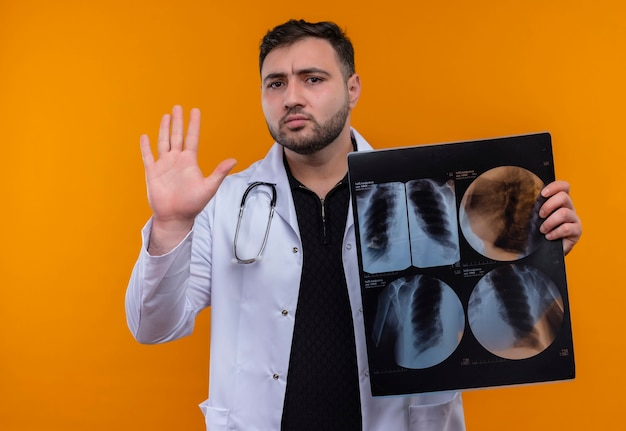手で一時停止の標識を作る肺のx線を保持聴診器で白衣を着て若いひげを生やした男性医師