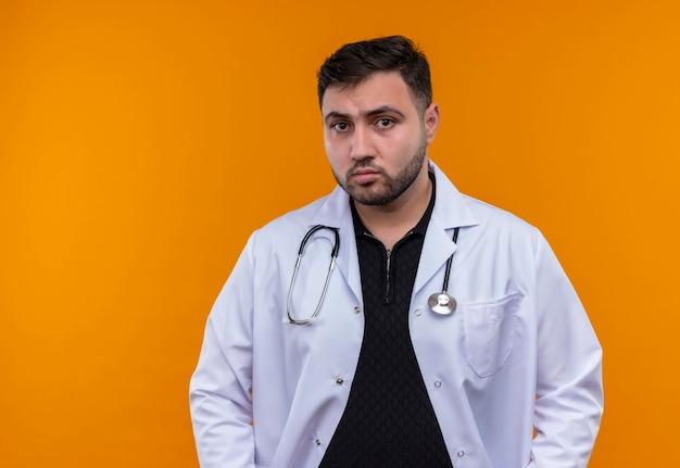 真面目な顔でカメラに向かって聴診器で白衣を着た若いひげを生やした男性医師