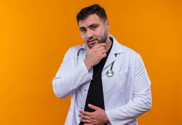 聴診器で白衣を着た若いひげを生やした男性医師が顔に物思いにふける表情で顎に手でカメラを見て