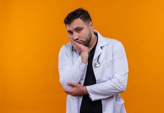 物思いにふける表情で顎に手でカメラを見て聴診器で白衣を着た若いひげを生やした男性医師