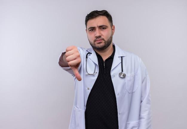 Молодой бородатый мужчина-врач в белом халате со стетоскопом выглядит недовольным, показывая неприязнь