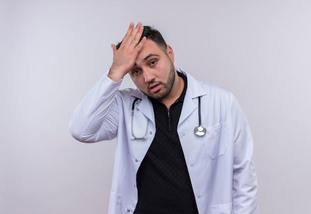 Молодой бородатый мужчина-врач в белом халате со стетоскопом выглядит усталым и скучающим с головной болью
