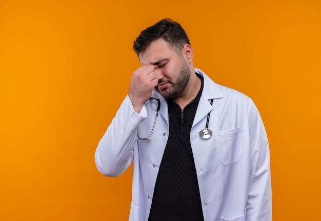 聴診器で白衣を着た若いひげを生やした男性医師は、目を閉じて疲れて退屈な鼻に触れているように見えます