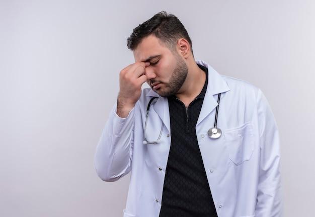 Giovane maschio barbuto medico indossa camice bianco con lo stetoscopio cercando stanchi e annoiati toccando il naso tra gli occhi chiusi