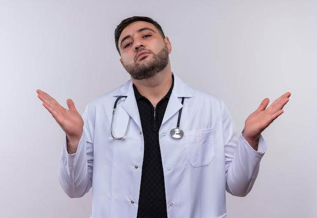 Молодой бородатый мужчина-врач в белом халате со стетоскопом выглядит неуверенным и смущенным, разводя руки в стороны