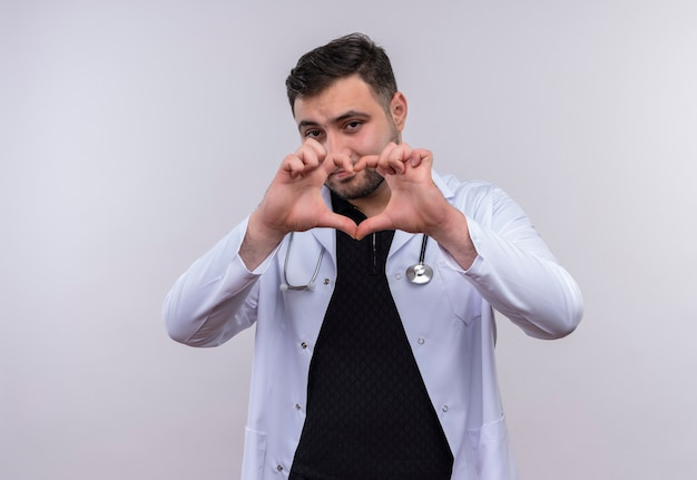指で心臓のジェスチャーをする聴診器で白衣を着ている若いひげを生やした男性医師