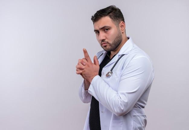 Молодой бородатый мужчина-врач в белом халате со стетоскопом делает пистолетный жест с уверенными пальцами