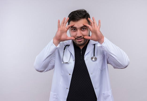 Young bearded male doctor wearing white coat with stethoscope opnening eyes with fingers