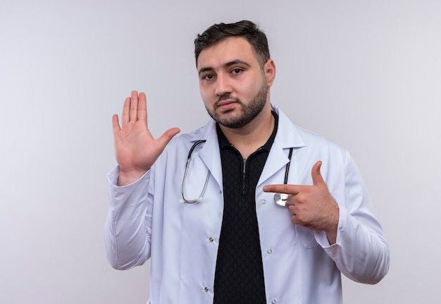 聴診器で白衣を着て、自信を持って見える人差し指で腕を指している若いひげを生やした男性医師