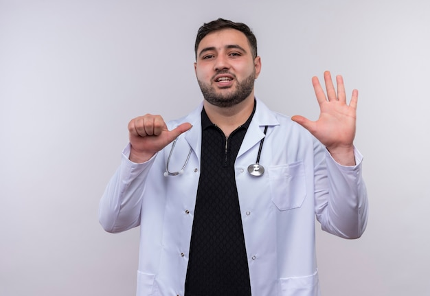 Young bearded male doctor wearing white coat with stethoscope showing and pointing up with fingers number six