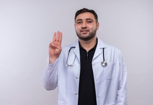 Giovane maschio barbuto medico indossa camice bianco con lo stetoscopio che mostra e rivolto verso l'alto con le dita numero tre sorridente