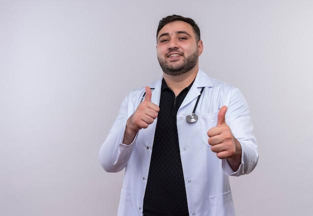 聴診器で白衣を着た若いひげを生やした男性医師は、顔に幸せな笑顔で親指を示しています