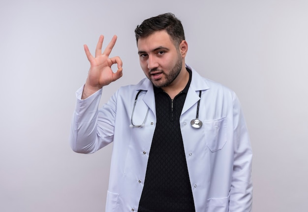 聴診器と白いコートを着て笑顔の若いひげを生やした男性医師は、白い背景の上にokサインをやっています