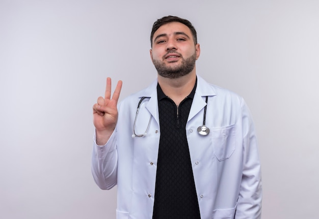 Young bearded male doctor wearing white coat with stethoscope smiling showing number two or victory sign