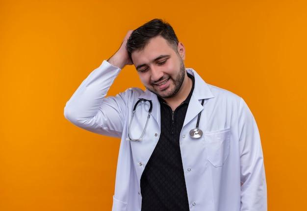 Giovane maschio barbuto medico indossa camice bianco con lo stetoscopio toccando la testa per errore, fotgot, concetto di cattiva memoria