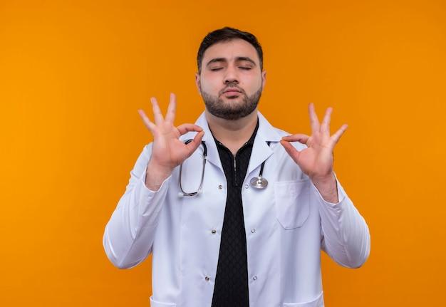 目を閉じてリラックスした聴診器で白衣を着て、指で瞑想の兆候を作る若いひげを生やした男性医師