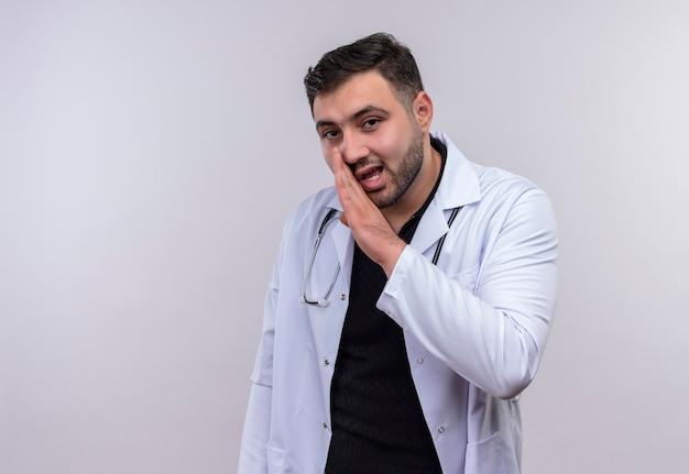 口の近くの手で秘密を告げる白衣を着た若いひげを生やした男性医師
