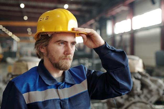 산업 공장에서 일하는 동안 카메라 앞에 서 있는 보호용 헬멧을 쓴 젊은 수염 난 남성 엔지니어 또는 공장 노동자