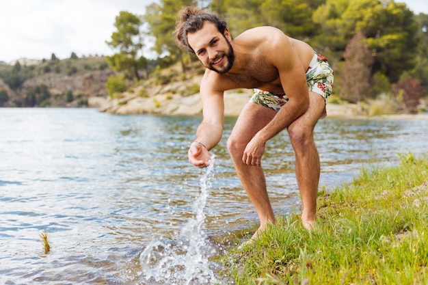 Young bearded male having fun on lake