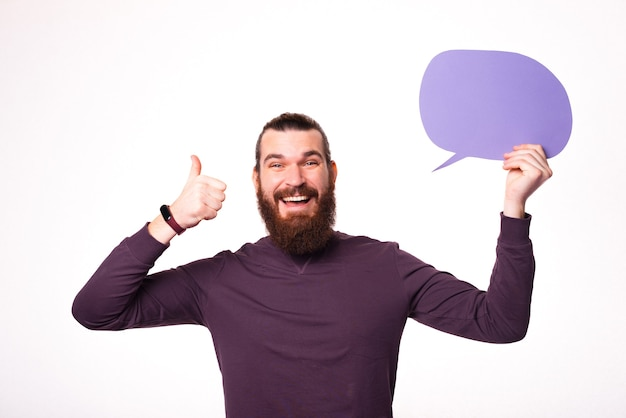 Young bearded male is smiling at the camera and holding a speech bubble and showing a thumb up