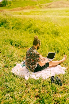 Young bearded male sitting with laptop in field