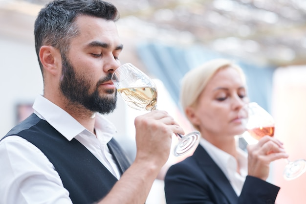 Young bearded male sommelier and his female colleague smelling new sorts of wine in wineglasses before tasting it