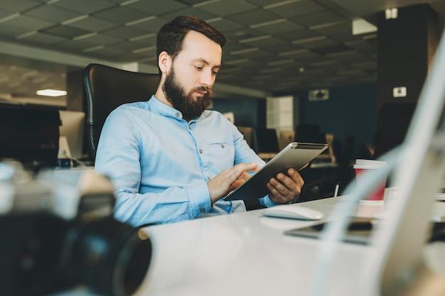 사진 카메라와 함께 사무실에서 책상에 앉아 태블릿을 사용하는 젊은 수염 난된 남성