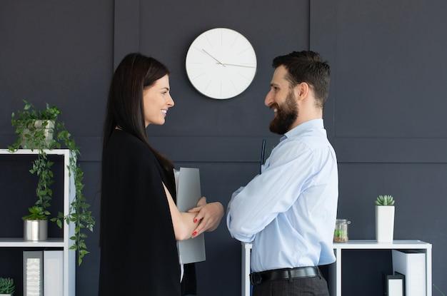 Молодой бородатый мужчина и женщина в формальной одежде обсуждают что-то, держа папку с документами