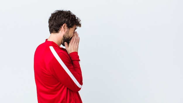 Young bearded man back view feeling worried, hopeful and religious, praying faithfully with palms pressed, begging forgiveness over copy space wall