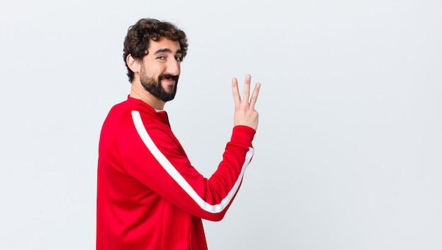 Молодой бородатый мужчина вид сзади улыбается и выглядит дружелюбно, показывая номер три или треть рукой вперед, считая вниз на стене с копией пространства