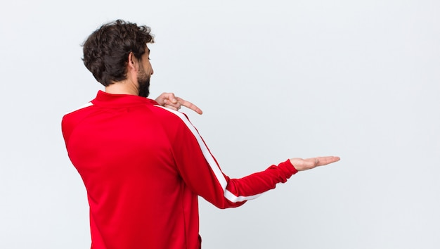 Young bearded man back view smiling, feeling happy, carefree and satisfied, pointing to concept or idea on copy space on the side against copy space wall