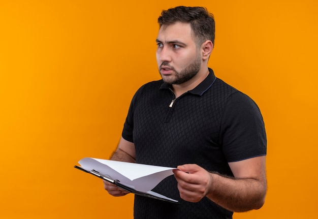 Giovane uomo barbuto in camicia nera che tiene appunti guardando da parte con espressione confusa