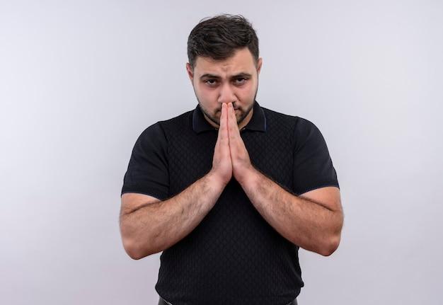 Giovane uomo barbuto in camicia nera che tengono le mani come pregare preoccupato ed emotivo