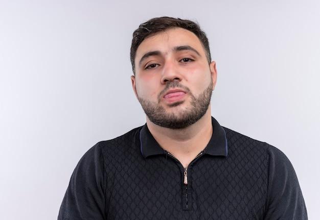 Giovane uomo barbuto in camicia nera che tiene misura guardando la telecamera con la lingua fuori