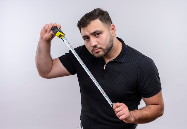 Young bearded man in black shirt holding measure tape looking at camera with serious face