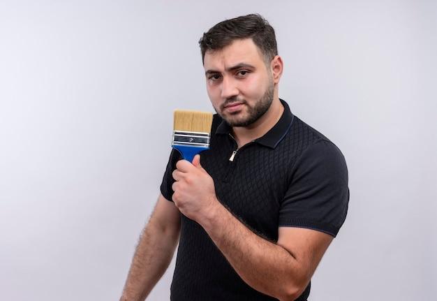 Giovane uomo barbuto in camicia nera che tiene il pennello che guarda l'obbiettivo con seria espressione fiduciosa