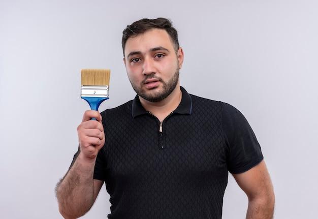 Giovane uomo barbuto in camicia nera tenendo il pennello che guarda l'obbiettivo con la faccia seria