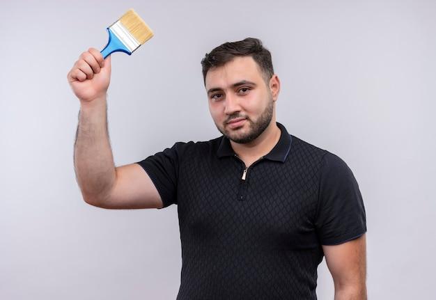 Giovane uomo barbuto in camicia nera tenendo il pennello alzando la mano che guarda l'obbiettivo con un sorriso