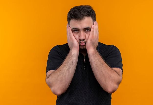 Giovane uomo barbuto in camicia nera che guarda l'obbiettivo volto toccante sorpreso e stupito con le braccia