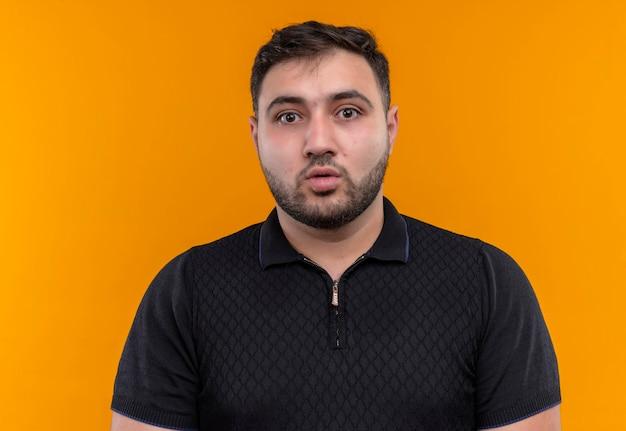 Giovane uomo barbuto in camicia nera che guarda l'obbiettivo sorpreso e stupito