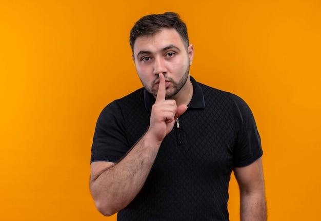 Giovane uomo barbuto in camicia nera che fa gesto di silenzio con il dito sulle labbra